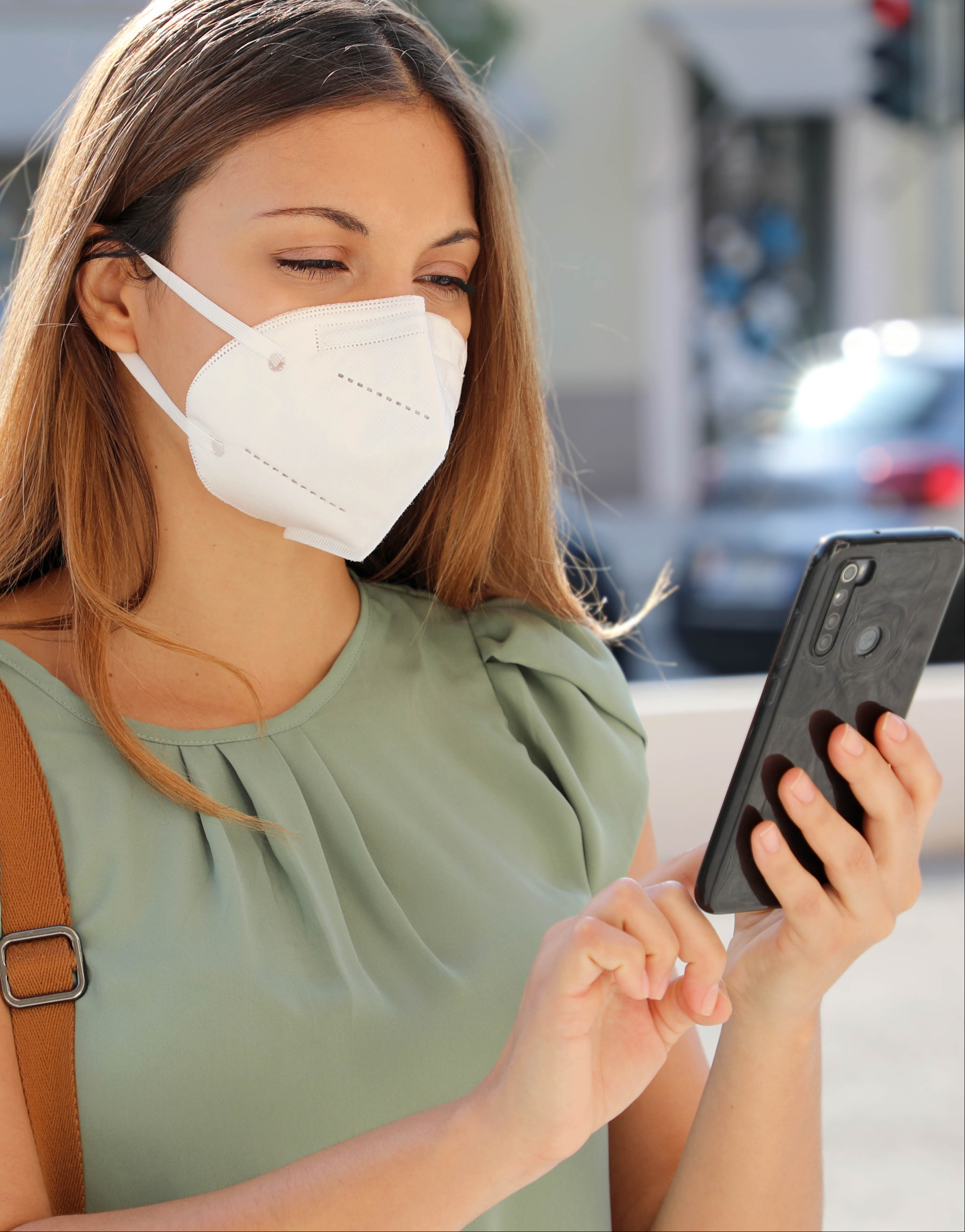 Image: woman wearing facemask using a mobile app